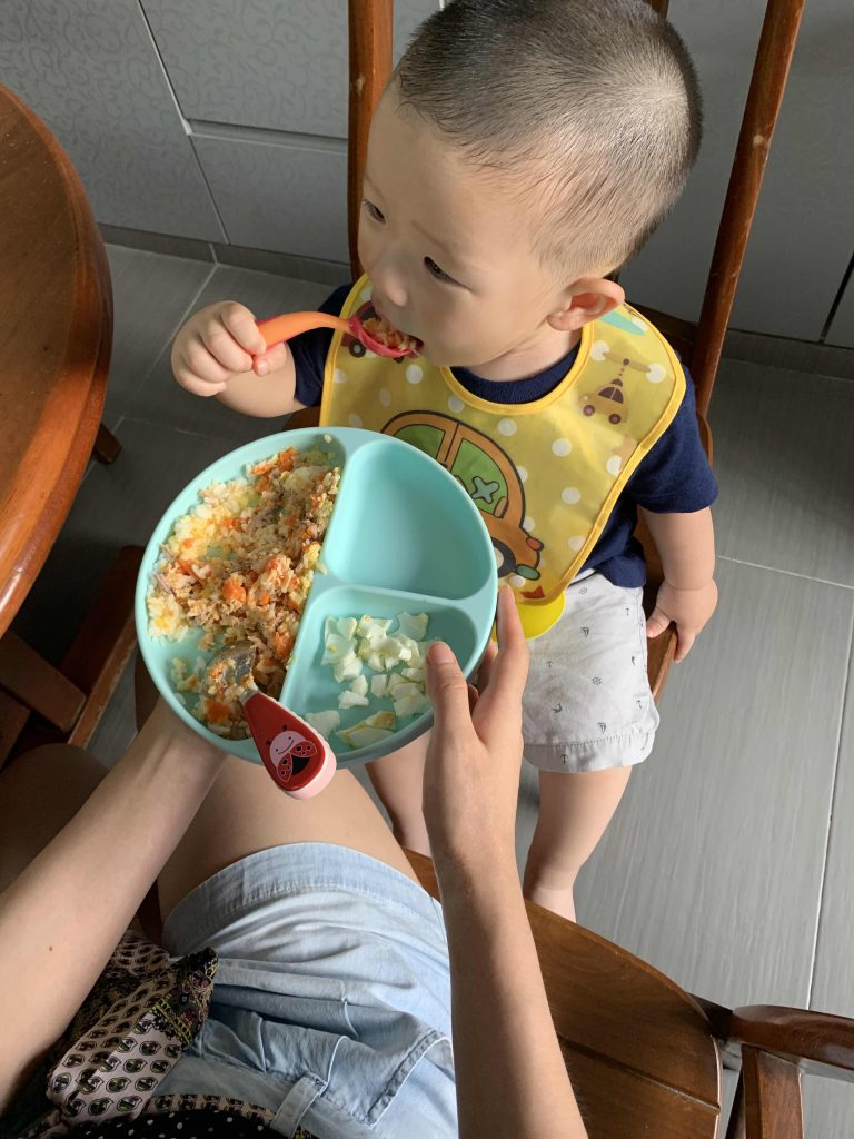 Practising to eat his own meal at Grandpa and Grandma home!